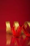 Rood en gouden lint op donkerrode achtergrond met ruimte voor tekst Royalty-vrije Stock Foto's