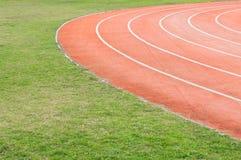 Rood en groen. Atletisch gebied met groen gras Royalty-vrije Stock Fotografie