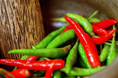 Rood en groene paprika in mortier Stock Afbeelding