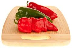 Rood en groene paprika's op een raad Royalty-vrije Stock Afbeeldingen