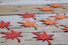 Rood en Oranje Autumn Leaves Paper Origami Background op de houten lijst stock afbeeldingen