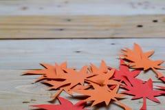 Rood en Oranje Autumn Leaves Paper Origami Background op de houten lijst royalty-vrije stock afbeelding