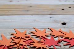 Rood en Oranje Autumn Leaves Paper Origami Background op de houten lijst royalty-vrije stock foto