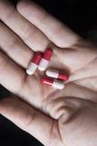 Rood en roze antibioticum op mensenhand Stock Afbeeldingen