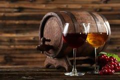 Rood en wit wijnglas met fles en vat op de bruine houten achtergrond stock afbeeldingen