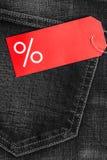 Rood etiket met percententeken op denim Stock Foto