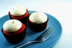3 rood Fluweel cupcakes op een blauwe plaat en een vork Stock Fotografie