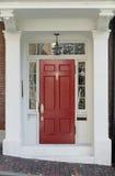 Rood Front Door met Wit Deurkader en Vensters op Baksteenstraat Stock Afbeelding