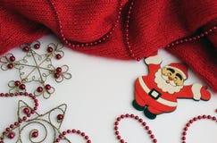 Rood gebreid stuk op een lichte achtergrond met parels van rode kleur Nabijgelegen leugens het cijfer van Santa Claus stock afbeeldingen