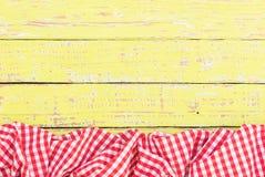 Rood gecontroleerd gekreukt tafelkleed op rustieke houten lijstoppervlakte, hoogste mening royalty-vrije stock foto