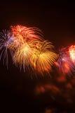 Rood, geel en blauw vuurwerk tegen een zwarte hemel Stock Foto