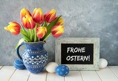 Rood-gele tulpen in blauwe ceramische waterkruik met paaseieren en a Royalty-vrije Stock Foto's