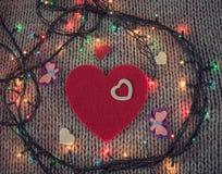 Rood gevoeld hart met kleurrijke vlinders, kleurrijke slinger met Stock Fotografie