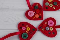 Rood gevoelde hartenambachten die met parels en knopen op witte achtergrond worden verfraaid Royalty-vrije Stock Afbeeldingen