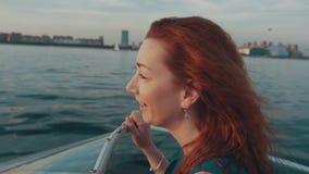 Rood haarmeisje in de turkooise bespreking van de de motorboot van de kledingsaandrijving met jongen De avond van de zomer stock video