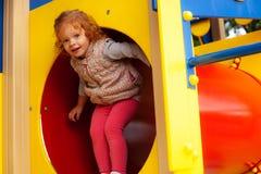 Rood haarmeisje die door de tunnel in de speelplaats kruipen stock foto's