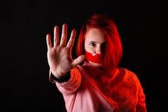 Rood haarmeisje in donkere studio met rode kleurenkleren, dicht portret, vrouw in t-shirt en jeans Gezicht met Plakband op mond stock foto's