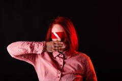 Rood haarmeisje in donkere studio met rode kleurenkleren, dicht portret, vrouw in t-shirt en jeans Gezicht met Plakband op ogen C stock foto's