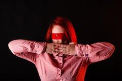 Rood haarmeisje in donkere studio met rode kleurenkleren, dicht portret, vrouw in t-shirt en jeans Gezicht met Plakband op ogen C royalty-vrije stock afbeeldingen