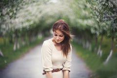 Rood haired meisje in appelsteeg op de wind Royalty-vrije Stock Afbeeldingen