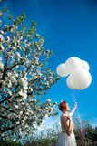 Rood haired meisje die massieve heliumballons houden stock afbeelding