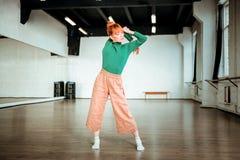 Rood haired meisje in een groene col die yoga doen een gymnastiek royalty-vrije stock afbeeldingen