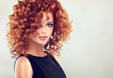 Rood haired meisje met krullend kapsel stock foto's