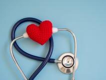 Rood hart die diepe blauwe stethoscoop op de blauwe achtergrond met behulp van Concept liefde en gevende patiënt door het hart Ex Stock Foto's