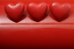 Rood hart drie op rode achtergrond Stock Afbeelding