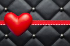 Rood hart en lint op zwart gewatteerd leer stock afbeelding