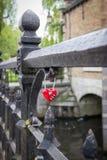 Rood hart gevormd liefdehangslot op de brug in Brugge, België stock afbeeldingen