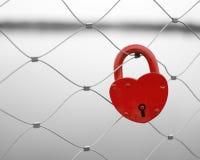 Rood hart gevormd liefdehangslot op een brugomheining. Stock Foto