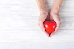 Rood hart in handen op witte houten achtergrond Stock Afbeeldingen