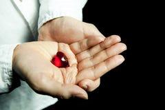 Rood hart in handen. zwarte achtergrond. Stock Foto
