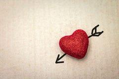 Rood hart met cupidopijl op kartonachtergrond Het behang van de valentijnskaart royalty-vrije stock afbeelding