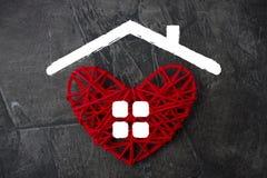 Rood hart met een dak en vensters in de vorm van een huis Thema van huisvesting royalty-vrije stock afbeeldingen