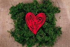 Rood hart met een patroon op groen mos royalty-vrije stock afbeeldingen