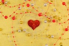 Rood hart met parels op een gouden achtergrond stock afbeelding