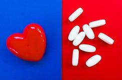 Rood hart met pillen op een rode en blauwe achtergrond stock fotografie
