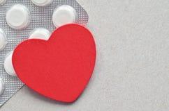 Rood hart met verpakking van tabletten Stock Afbeeldingen