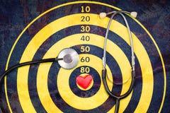 Rood hart op dartboard met barst en stethoscoop stock fotografie