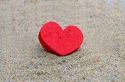Rood hart op de zandoppervlakte royalty-vrije stock afbeeldingen