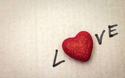 Rood hart op kartonachtergrond Het behang van de valentijnskaart royalty-vrije stock foto's