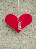 Rood hart van het houten hangen op een glanzende draad op de achtergrond van de textuur van abstract klein steenbeton royalty-vrije stock afbeeldingen