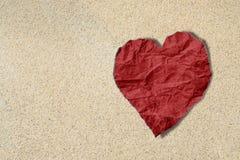Rood hart verfrommeld document op zandtextuur, de textuurachtergrond van de strandminnaar Stock Foto