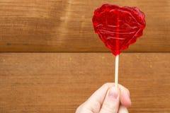 Rood hart in vrouwelijke hand op bruine achtergrond Stock Foto