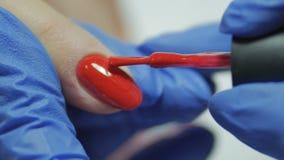 Rood het gelnagellak van de manicuredekking stock video