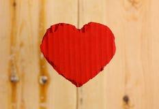 Rood het kartonhart van liefdevalentijnskaarten op ruwe pijnboomachtergrond Stock Afbeeldingen