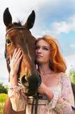 Rood hoofdmeisje en een paard Royalty-vrije Stock Afbeeldingen