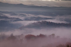 Rood-Hued ochtendmist over rokerige bergen stock foto